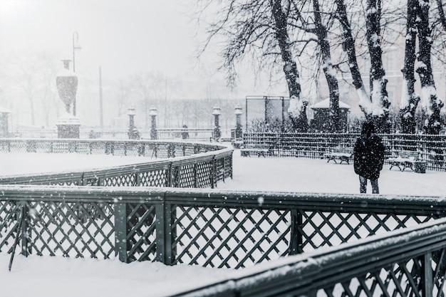 Un hombre irreconocible retrocede y camina por un jardín nevado de verano en san petersburgo