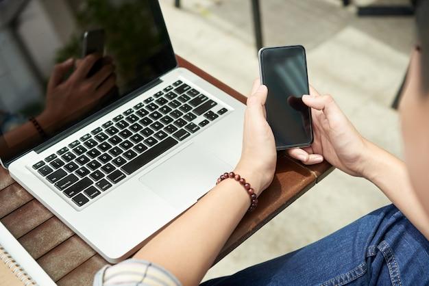 Hombre irreconocible sentado con laptop en café y usando smartphone