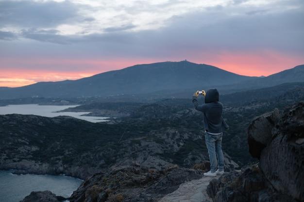 Hombre irreconocible en sudadera con capucha se encuentra en la cima de la ruta de senderismo en la montaña