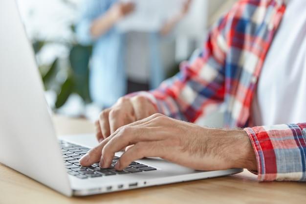 Hombre irreconocible trabaja en una computadora portátil portátil moderna, instala una nueva aplicación