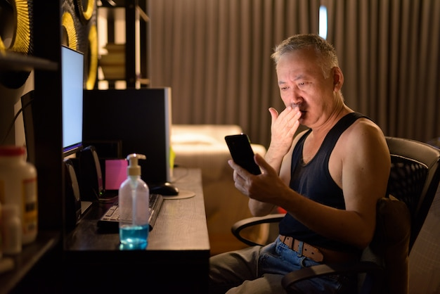 Hombre japonés maduro estresado que usa el teléfono y recibe malas noticias mientras trabaja desde casa