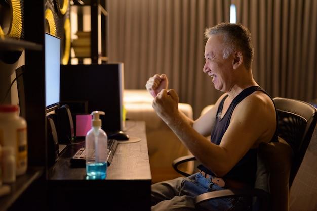 Hombre japonés maduro feliz usando la computadora y recibiendo buenas noticias en casa