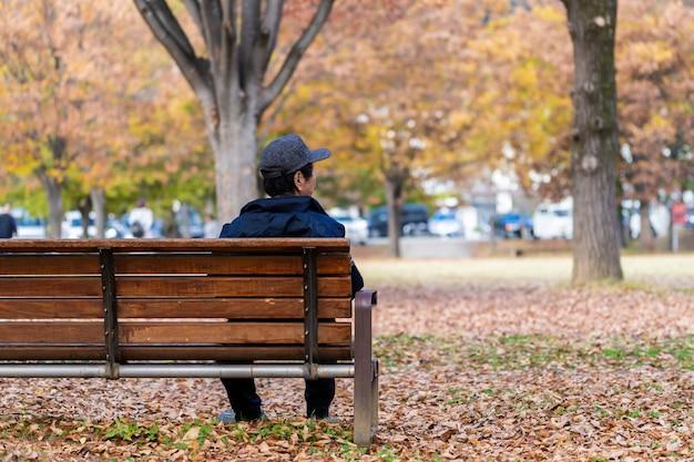 Hombre japonés mayor solo que descansa sobre un banco en el parque en la estación del otoño