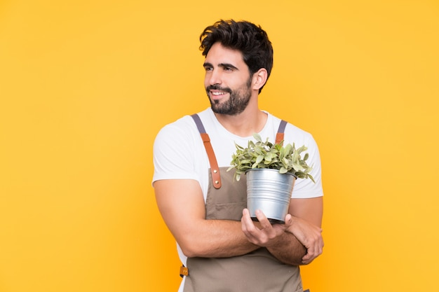 Hombre jardinero con barba sobre pared amarilla aislada mirando hacia el lado