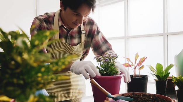 Hombre jardinero feliz cuidando flor en una maceta.