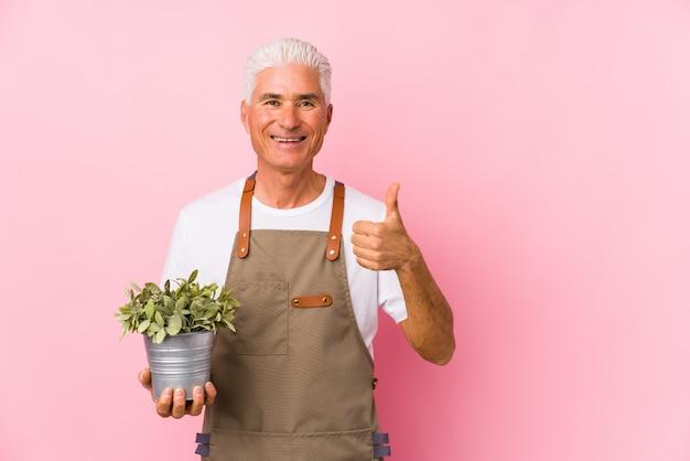 Hombre de jardinero de mediana edad aislado sonriendo y levantando el pulgar hacia arriba