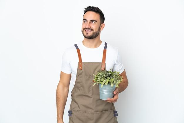 Hombre jardinero sosteniendo una planta aislada pensando en una idea mientras mira hacia arriba