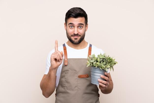 Hombre jardinero sosteniendo una planta sobre señalar con el dedo índice una gran idea