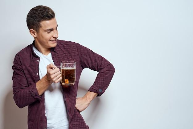 Hombre con una jarra de cerveza divertida camisa de estilo de vida alcohol fondo claro.