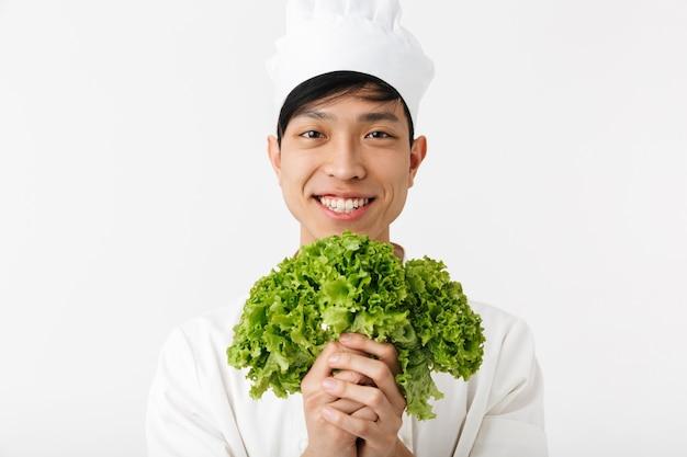 Hombre jefe alegre asiático en uniforme de cocinero blanco sonriendo a la cámara mientras sostiene ensalada de lechuga verde aislado sobre la pared blanca