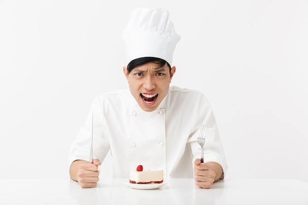Hombre jefe asiático nervioso en uniforme de cocinero blanco gritando mientras come sabroso pastel de queso aislado sobre la pared blanca