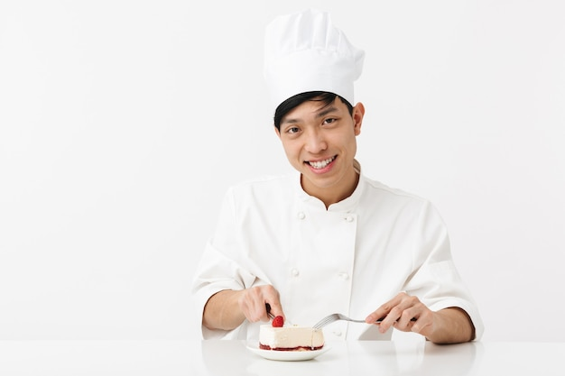 Hombre jefe asiático satisfecho en uniforme de cocinero blanco sonriendo a la cámara mientras come sabroso pastel de queso aislado sobre la pared blanca