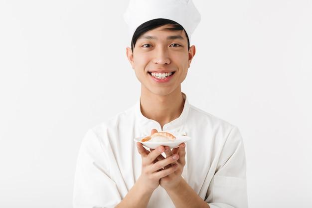 Hombre jefe chino complacido en uniforme de cocinero blanco sonriendo a la cámara mientras sostiene un plato con mariscos sushi aislado sobre una pared blanca