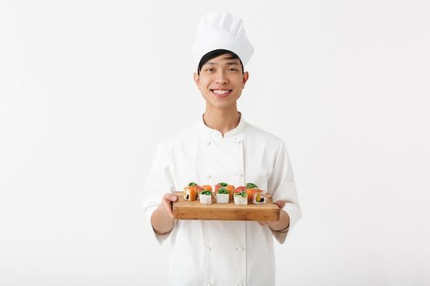 Hombre jefe chino positivo en uniforme de cocinero blanco sonriendo a la cámara mientras sostiene el plato con sushi set aislado sobre la pared blanca
