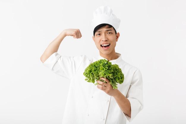 Hombre jefe guapo asiático en uniforme de cocinero blanco sonriendo a la cámara mientras sostiene ensalada de lechuga verde aislado sobre la pared blanca