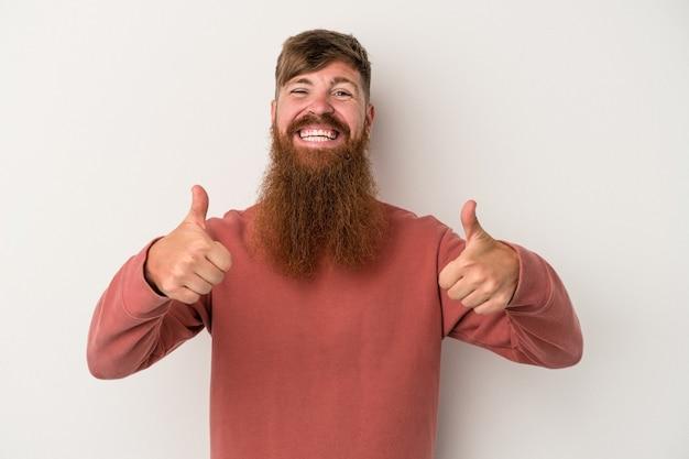 Hombre de jengibre caucásico joven con barba larga aislado sobre fondo blanco sonriendo y levantando el pulgar hacia arriba