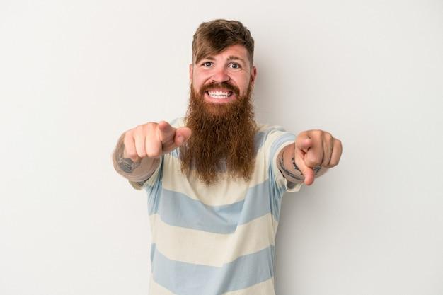 Hombre de jengibre caucásico joven con barba larga aislado sobre fondo blanco sonrisas alegres apuntando al frente.