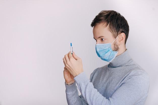 Hombre con jeringa se prepara para la inyección. médico profesional con jeringa médica en manos listas para inyección. doctor en máscara médica tiene jeringa con vacuna.