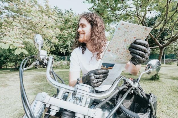 Hombre de jinete guapo deportivo motorista en camiseta blanca en blanco comprueba un mapa para viajar. bicicleta vintage personalizada. estilo de vida urbano. retrato al aire libre.