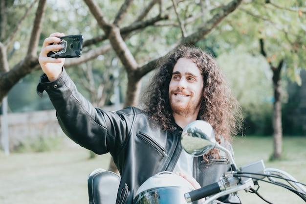 Hombre de jinete guapo deportivo motorista en camiseta blanca en blanco tomando un selfie. bicicleta vintage personalizada. estilo de vida urbano. retrato al aire libre.