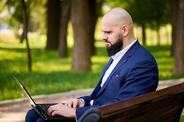 Hombre joven acertado con la computadora portátil en el parque.