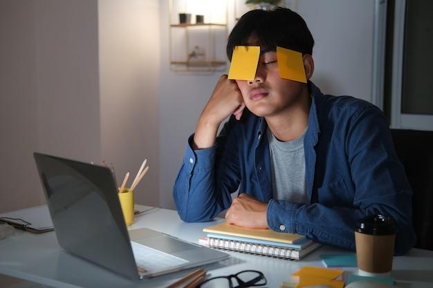 Hombre joven adicto al trabajo cansado agotado con nota adhesiva.