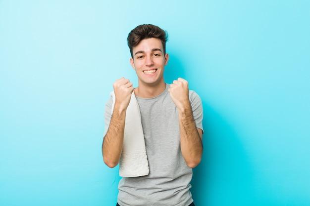 Hombre joven del adolescente de la aptitud que anima despreocupado y emocionado. concepto de victoria