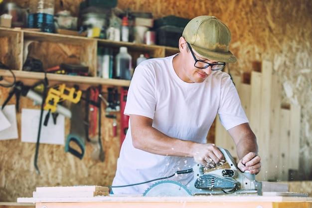 Hombre joven adulto que trabaja en una carpintería trabajando con herramientas en el producto