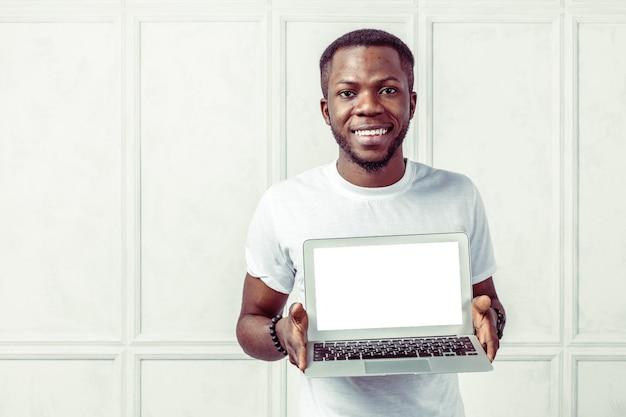 Hombre joven africano que sostiene el ordenador portátil