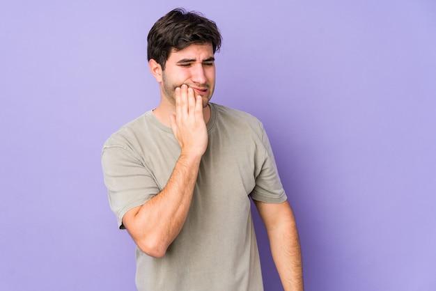 Hombre joven aislado en púrpura con un fuerte dolor de dientes, dolor molar.