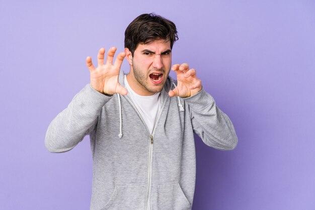 Hombre joven aislado en púrpura mostrando garras imitando a un gato, gesto agresivo.