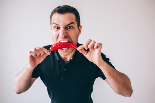 Hombre joven aislado sobre fondo. emocional chico morder ají pimiento rojo caliente con dientes. listo para comer. grita y grita.