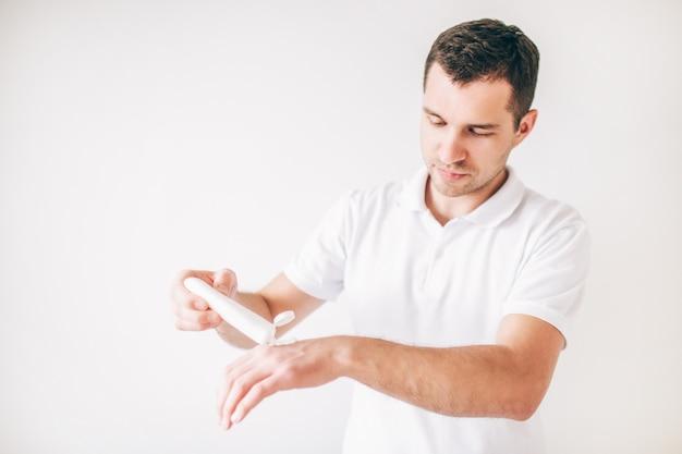 Hombre joven aislado sobre la pared blanca. guy humectante manos con crema. cuida la piel y las palmas.