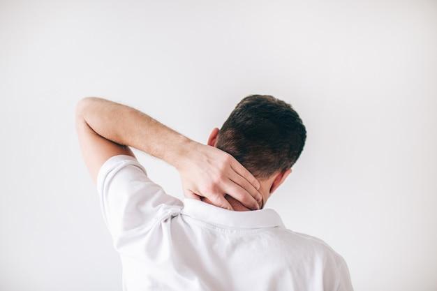 Hombre joven aislado sobre la pared blanca. vista posterior del chico tiene problemas con el cuello. doloroso y dolorido. hombre sostenga la mano en la parte posterior de su cuello.