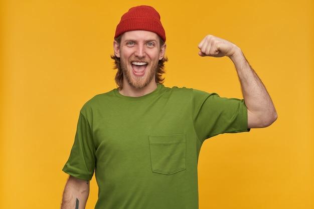 Hombre joven, alegre con cabello rubio, barba y bigote. vistiendo camiseta verde y gorro rojo. tiene tatuaje. muestra sus bíceps, fuerza. aislado sobre pared amarilla