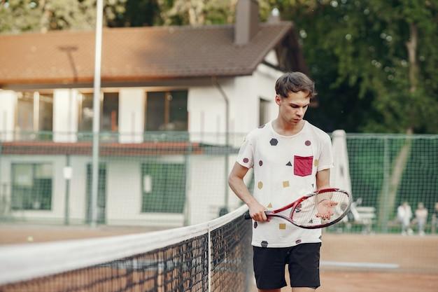 Hombre joven alegre en camiseta. chico sosteniendo pelota y raqueta de tenis.