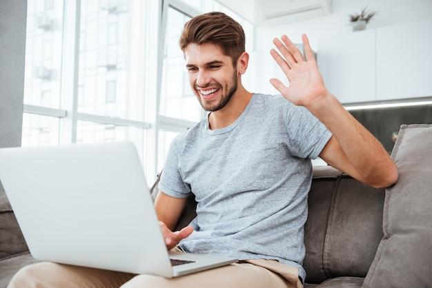 Hombre joven alegre en camiseta sentado en el sofá en casa. trabajando en la computadora portátil mientras saluda y sonríe.