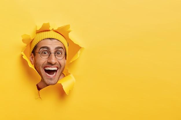 Hombre joven alegre divertido mira a través del agujero de papel rasgado