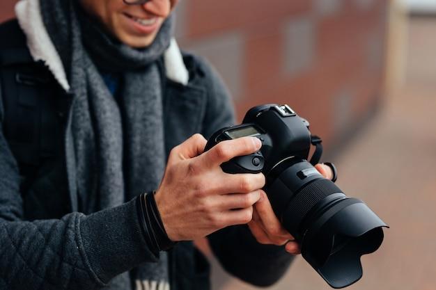 Hombre joven alegre mira fotos en la cámara. vestida chaqueta con estilo, gris, bufanda