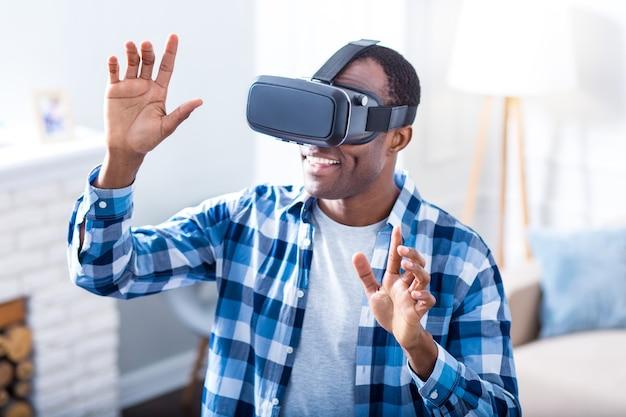 Hombre joven alegre positivo sonriendo y con gafas 3d mientras usa tecnología virtual
