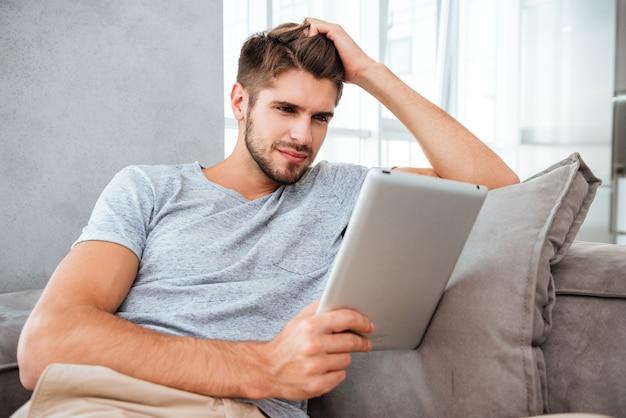 Hombre joven alegre que mira la tableta mientras está sentado en el sofá