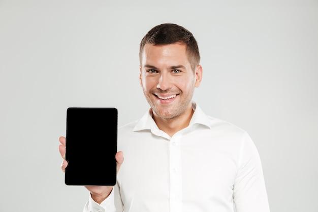 Hombre joven alegre que muestra la pantalla de la tableta.