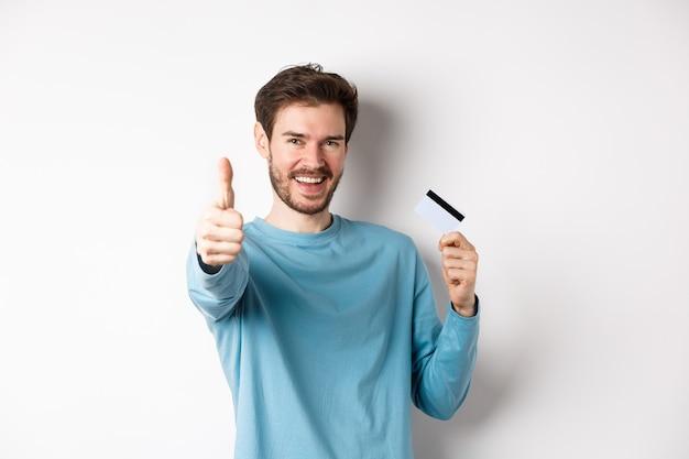 Hombre joven alegre que muestra la tarjeta de crédito plástica y el pulgar hacia arriba, como y aprueban un buen servicio bancario, de pie sobre fondo blanco.