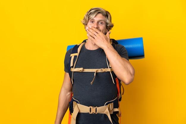 Hombre joven alpinista aislado appy y sonriente cubriendo la boca con la mano
