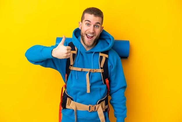 Hombre joven alpinista caucásico con una gran mochila aislada