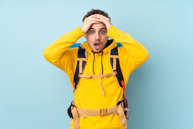 Hombre joven alpinista con una gran mochila aislada en azul con expresión facial sorpresa