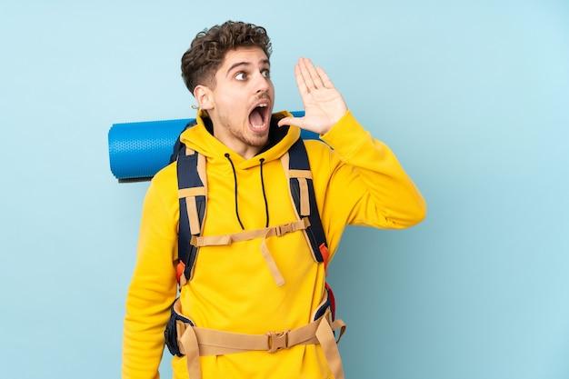 Hombre joven alpinista con una gran mochila aislada en azul gritando con la boca abierta
