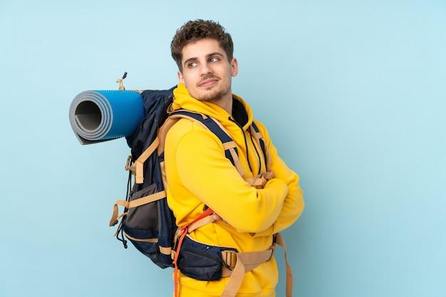 Hombre joven alpinista con una gran mochila aislada en azul riendo
