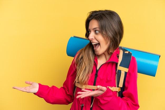 Hombre joven alpinista con una gran mochila aislada sobre fondo amarillo con expresión de sorpresa mientras mira de lado