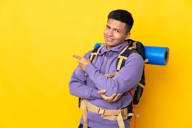 Hombre joven alpinista con una gran mochila aislada